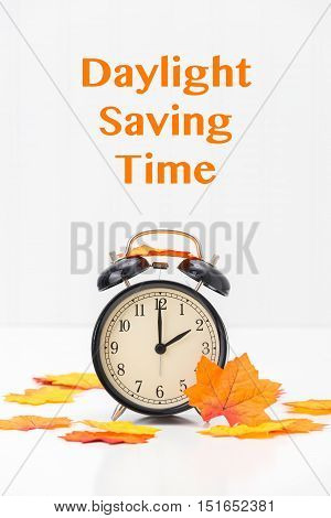 Black retro alarm clock and autumn leaves reminder to turn back clocks.