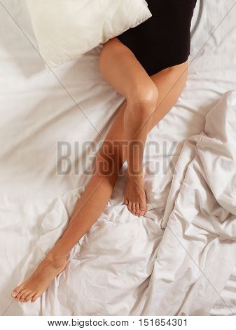 Closeup of sexy female legs on the bed. Woman lazy girl relaxing lazing in bedroom.