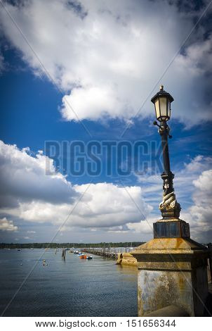 Fluffy white cumulus clouds float in deep blue skies over a jetty and a Victorian lamp post in Poole Harbour at Sandbanks