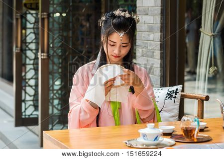 Chengdu Sichuan Province China - Sept 24 2016 : Chinese girl wearing traditional clothes at a table with some tea weaving in a street.