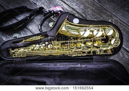 Part of golden alto saxophone in box