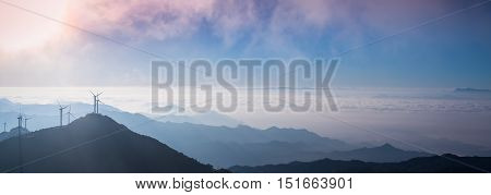 wind turbines in the morning and stretches of blue mountains background panoramic view