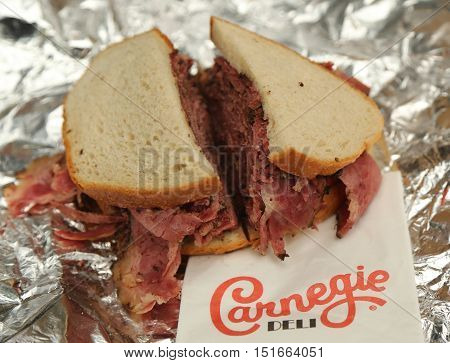 NEW YORK - OCTOBER 13, 2016: Famous Pastrami on rye sandwich served with pickles in Carnegie Deli in Midtown Manhattan