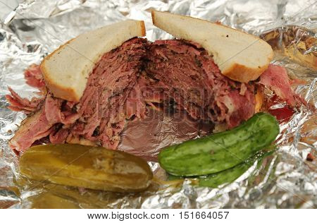 Famous Pastrami on rye sandwich served with pickles in New York Deli