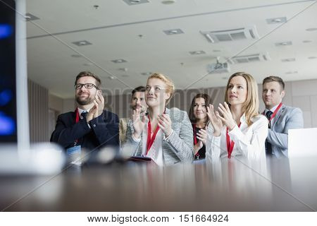 Confident business people applauding during seminar