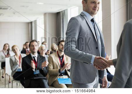Businessman greeting public speaker during seminar