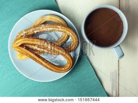 A plate of churros, traditional Spanish, especially Madrid, dessert, particularly for Sunday breakfast, with a cup of hot chocolate, shot from above on blue textures