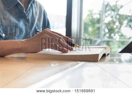 Man reading a book and writing notes on wooden table on sunset