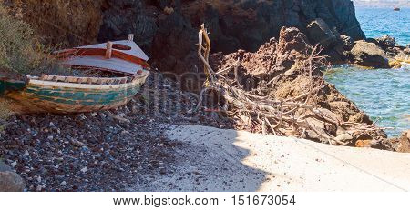 Old wooden broken boat is left on the rocky waterside of sea