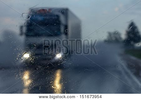 Truck in the rain,  view from a car windshield