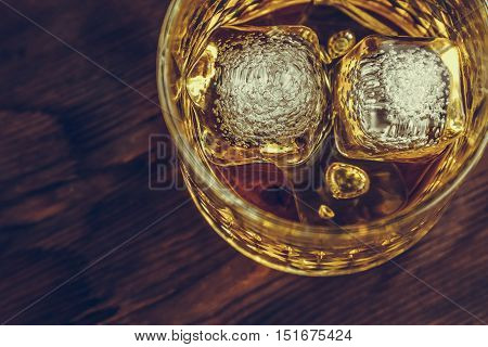 Top Of View Of Whiskey In Glass With Ice Cubes On Wood Table Background, Focus On Ice Cubes
