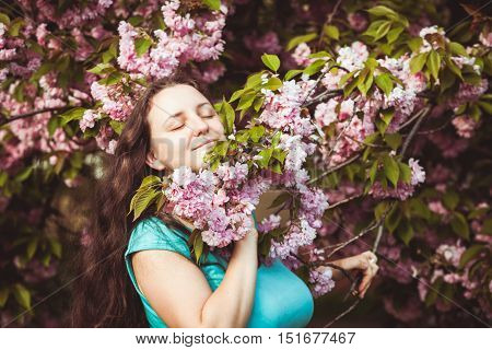 Usual happy woman portrain in the sakura blooming
