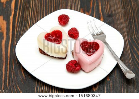 Panna cotta with raspberry jelly and fresh raspberries on a chocolate biscuit in the shape of heart