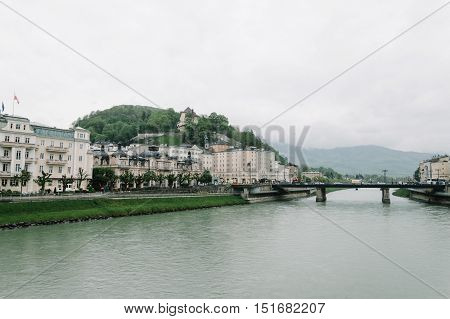 Salzburg Austria - April 30 2015: Salzach river and bridge. Salzburg is renowned for its baroque architecture and was the birthplace of Mozart. It is an Unesco World Heritage Site.