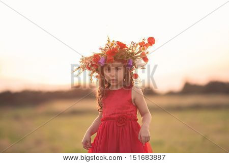 Beautiful smiling little girl in a red dress is spinning with a wreath on his head
