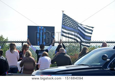 Maryland Heights MO USA - October 13 2016: Police firemen and a large crowd of civilians gather on a highway overpass to show respect to St. Louis County police officer Blake Snyder who was murdered while answering a domestic disturbance call on October 6