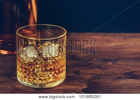 Glass Of Whiskey With Ice Cubes Near Bottle On Wood Table, Warm Atmosphere