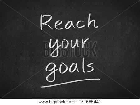 reach your goals text on blackboard background