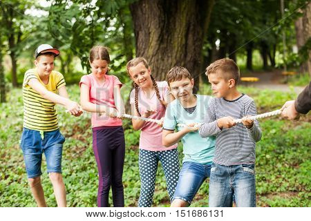 Group of happy smiling kids playing tug-of-war with rope in green park,
