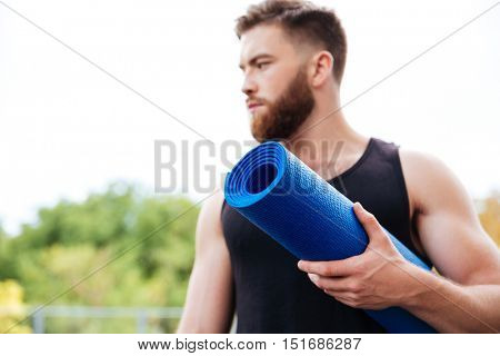 Serious male yoga instructor holding mat and looking away standing outdoors