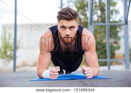 Young strong sportsman doing plank exercise on blue fitness mat during workout outdoors