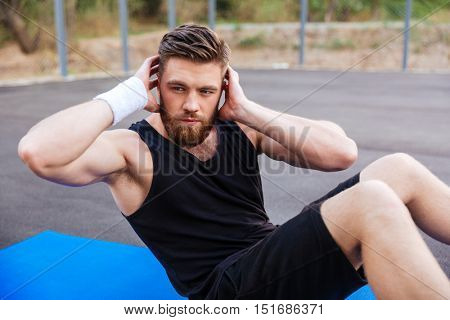 Young bearded sports man doing press exersices on the blue fitness mat outdoors