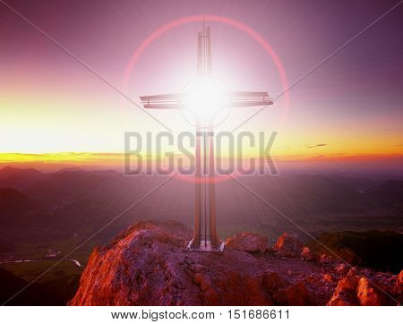Lens flare light strong effect. Cross on peak of Hoher Goell. Iron crucifix at mountain top in Alp at Austria Germany border. View to Tennen Range and Dachstein range Berchtesgaden Alps.