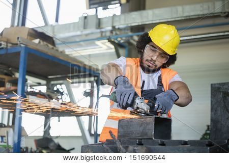 Young manual worker in protective workwear cutting metal in industry