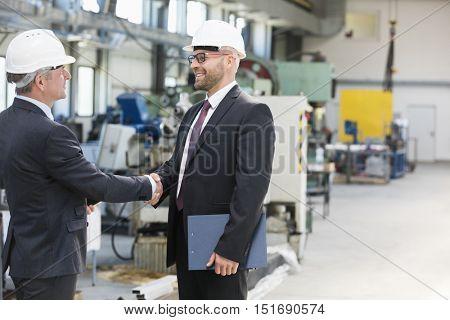 Businessmen shaking hands in metal industry