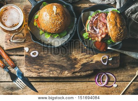 Homemade beef burgers with crispy bacon and fresh vegetables in small pans and glass of wheat beer on rustic serving board over shabby wooden background, top view, copy space, horizontal composition