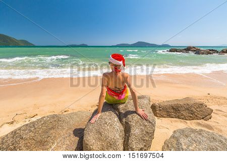 Beautiful, fashionable woman with red Santa Claus hat relaxing and catching tan on rocks of a tropical beach for xmas holiday in Laem Ka Beach, Phuket, Thailand.