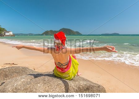 Christmas in the tropics. Beautiful woman with red Santa Claus hat enjoy and catching tan on rocks in tropical Laem Ka Beach for the Christmas holidays in Phuket, Thailand. Christmas vacation concept.