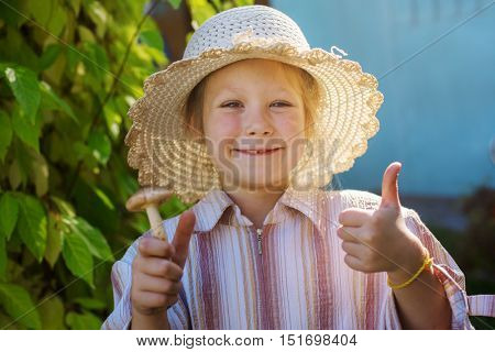 Happy child in a sunny autumn day with mushrooms in hands