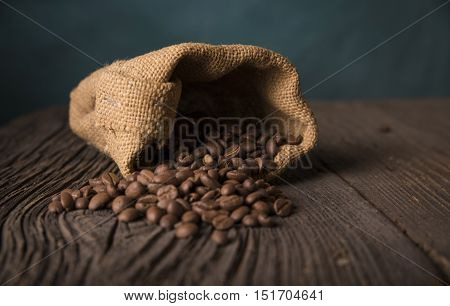Cup of coffee, bag and scoop on old rusty background