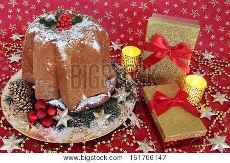 Italian pandoro christmas cake with holly, gift boxes, red and gold bauble decorations and candles on a red and gold star material background.