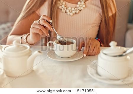 Woman With Tea. Hands Hold A Teaspoon. White Crockery On The Table.