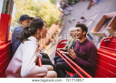 Happy Young Friends Having Fun On Amusement Park Ride