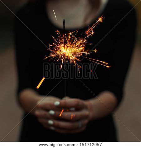 Young girl holding a sparkler. Beautiful sparks