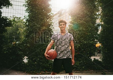 Portrait of young man holding a basketball on outdoor court. Smiling teenage streetball player looking at camera.