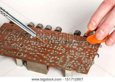 soldering iron in his hand on a white background