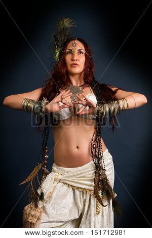 Performance. Young attractive retro model in old-fashioned wild clothing dancing. Tribe. Tattoo. Native savage woman