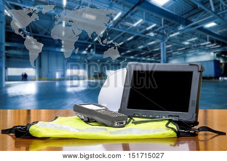 Rugged computers tablet and Bluetooth barcode scanner in front of modern warehouse with world map. Logistics concept.