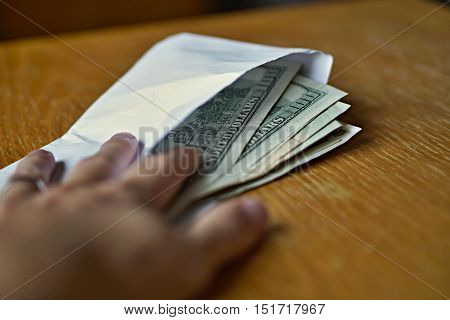 Male hand opening a white envelope full of American Dollars (USD, US Dollars) on the wooden table as a symbol of cash transfer, money laundering or bribery
