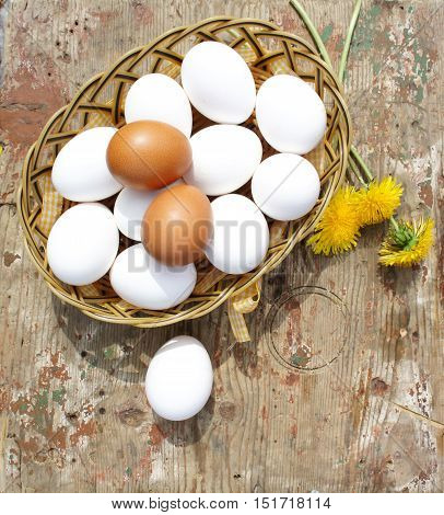 Eggs in a wicker basket on wooden background. Eggs in a wicker basket and dandelions on wooden background, top view