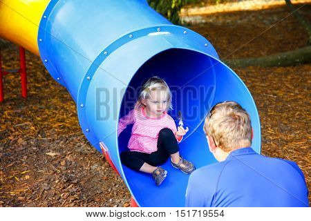 Loving father catching his little daughter at the slide. Little girl found a quill and show it to her father