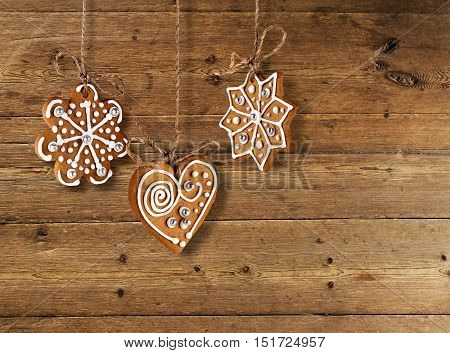 Decorated gingerbread cookies on old wooden plank background