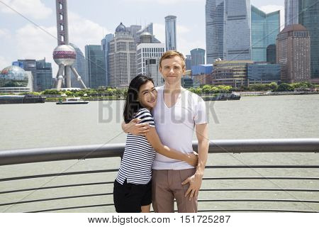 Portrait of smiling couple standing by railing with Shanghai skyline in background