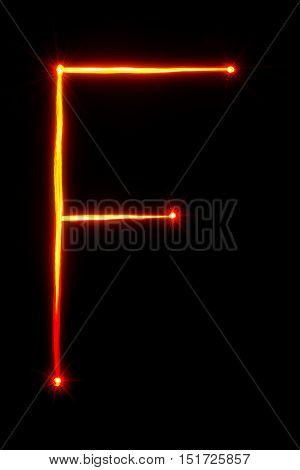 red light painting letter F on black background