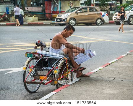 Yangon - September 9 2016: Tricycle taxis are still common and a practical way of transportation in Myanmar's capital Yangon. Here's a taxi driver who is reading a newspaper while waiting for customers.