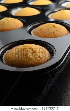 Freshly baked golden cupcakes just removed from oven. In paper cases iinside black bun tin resting on slate.